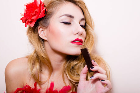 sensually: Funny pin up pretty girl attractive blond lady having fun sensually enjoying a bar of chocolate in studio over white or light copy space background closeup portrait picture Stock Photo
