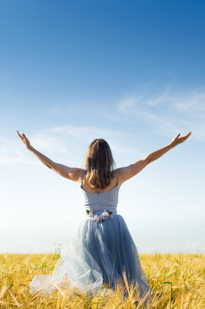 romantic fairy person: image of beautiful carefree blond young lady having fun wearing long blue ball dress with arms wide expand looking up on wheat field and blue sky background copyspace
