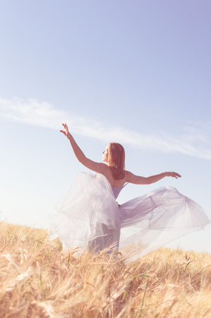 joy of romantic beauty fairy: image of beautiful blond young woman wearing long ball dress with arms wide open enjoying outdoors looking up on wheat field and blue sky background copy space photo