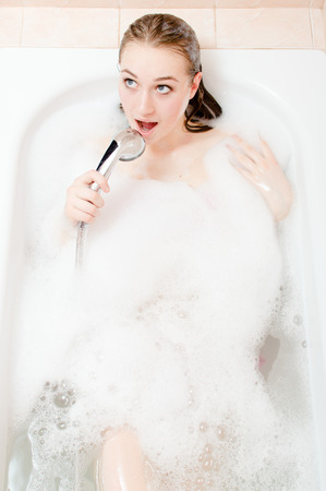 portrait of song & spa: closeup portrait of charming blond young woman having fun relaxing in bath with foam singing happy smile on white copy space background picture Stock Photo