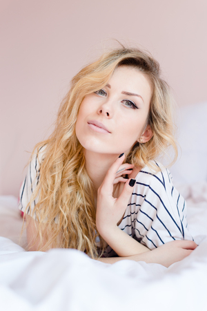 fashion glamor elegant blond young lady having fun relaxing lying in white bed gently smile looking at camera over light copy space wall background close up portrait picture photo