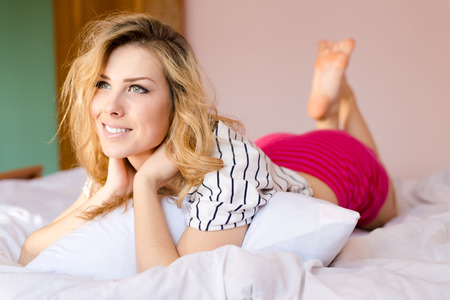 romantic blond young lady having fun relaxing lying in white bed happy smile & looking at copy space on pink wall bedroom background portrait picture photo