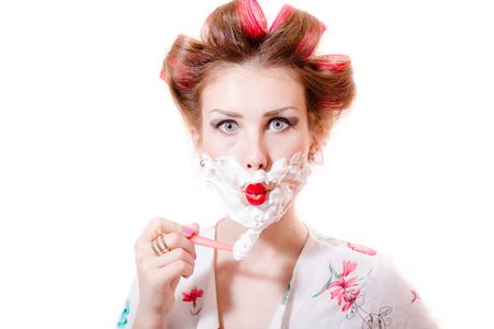 close up on beautiful young pinup lady having fun shaving face looking at camera isolated on white or light copy space background portrait picture Standard-Bild