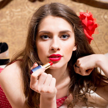 sensually: closeup portrait of seductive attractive sexual pinup girl with red flower in hair draws red lipstick open lips sensually looking at camera