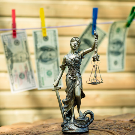 laundering: money laundering concept: image of Themis goddess or lady justice holding scale blindfold & USD dollar bank notes hanging on the copy space background Stock Photo