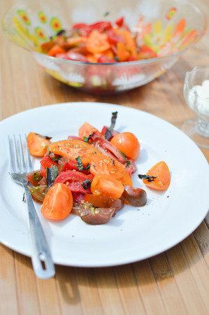 ensalada tomate: Tomato salad with green fresh basil on plate with fork