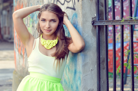 close up portrait of beautiful stylish fashion woman fair hair blond girl having fun gently smiling and looking at camera on graffiti wall city urban summer or spring outdoors copy space background Standard-Bild