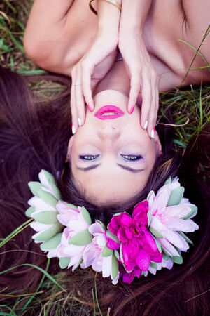 fairy girl: closeup on beautiful young lady having fun lying relaxing on green grass outdoors copy space background photo