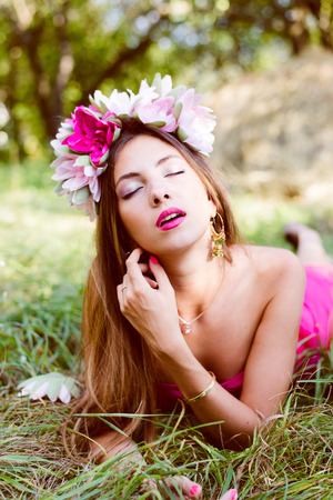 forest beautiful fairy: portrait of glamor fashion beauty model pretty girl having fun enjoying summer time wearing flower crown relaxing eyes closed on green grass copy space background photo