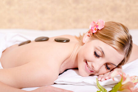 portrait of eyes closed pretty girl having fun happy smiling during spa procedures stone therapy massage & aromatherapy on white bed background photo
