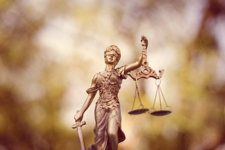 blind justice: sculpture of themis, femida or justice goddess on green leaves natural bokeh background Stock Photo