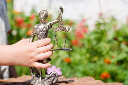 Kids hand holding sculpture of themis, femida or justice goddess on green leaves natural bokeh background
