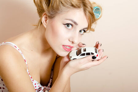 Beautiful elegant blond young pinup woman holding model toy car & looking at camera closeup portrait on light copy space background photo