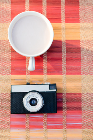 Cup of hot chocolate and retro film camera on orange background