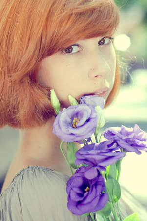 closeup portrait of beautiful romantic young woman holding blue rose flowers & sensually looking at camera on light copy space background photo