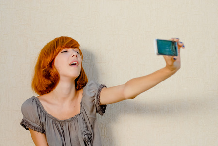 Young beautiful woman taking picture of herself on mobile touch phone photo