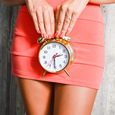 menstrual: closeup on alarm clock in hands of luxury slim pretty woman