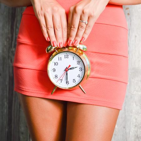 mini jupe: Gros plan sur un réveil dans les mains de jolie femme mince de luxe Banque d'images