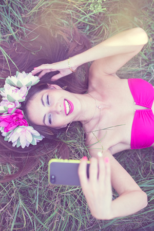 filtered image of beautiful brunette young lady in pink bikini and flower crown having fun making selfie picture lying on green grass outdoor Standard-Bild