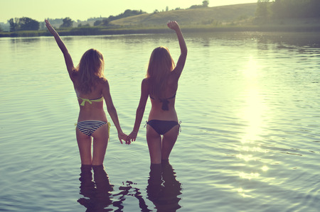 2 sexy pretty girls best girlfriends in bikini having fun together holding hands up to sky on summer sunset outdoors copy space background