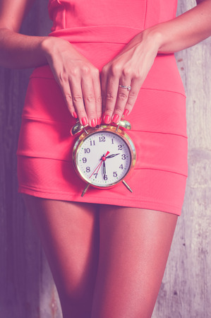 cystitis: luxury slim pretty woman holding alarm clock in front of her