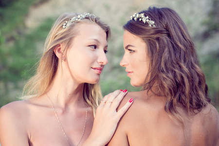 lesbian couple: closeup portrait of 2 brunette and blonde young pretty women best friends with bare shoulders wearing silver diadems looking at each other Stock Photo