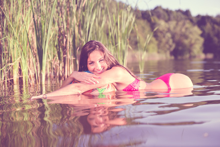 adult mermaid: beautiful brunette young female in bikini having fun relaxing in water lying on air ball on green summer outdoor