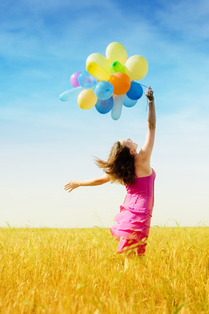 retro style photo: romantic blond young lady having fun holding air balloons flying in the field on summer blue sky outdoors copy space background photo