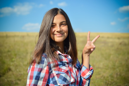 portrait of pretty teenage girl having fun showing peace sign happy smiling & looking at camera on green field under blue sky summer outdoors copy space background photo