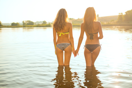 filtered image of 2 attractive young women or teenage girls best friends in bikini holding hands and looking at summer river or lake on outdoors copy space background Stockfoto