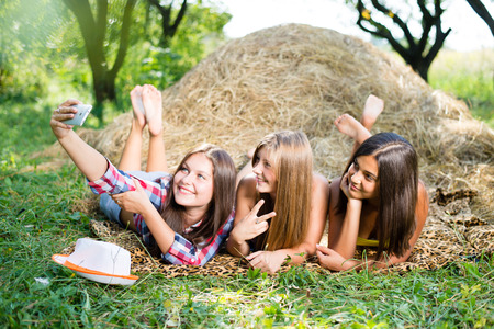 selfy: closeup portrait of 3 pretty girls having fun relaxing lying on hay happy smiling with excellent white teeth making selfie & looking at mobile phone on green summer outdoors copy space background Stock Photo
