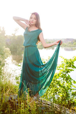 image of young woman beautiful brunette girl having fun standing in grass in green dress with pink wreath of flowers with wide-open arms against sun light & looking at outdoors copy space background