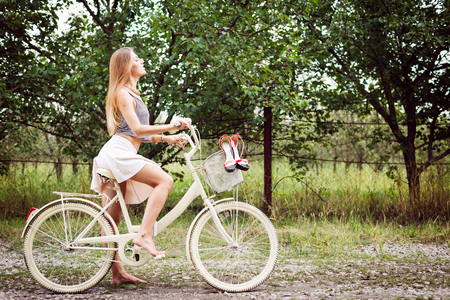 Young sexy pretty woman cycling on country road under bright blue summer sky copy space image Stock Photo