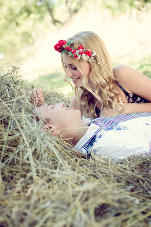 Portrait of happy young couple in bohemian style hugging on haystack on green outdoors background photo