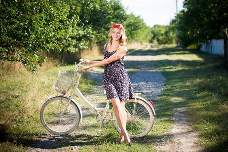 Young pretty girl in bohemian style outfit riding bicycle on summer day in countryside photo