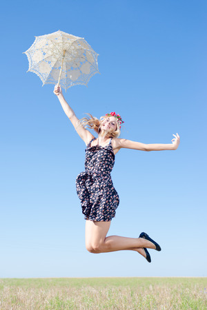 Portrait of happy young woman jumping high  with white lace umbrella against blue sky copy space background photo