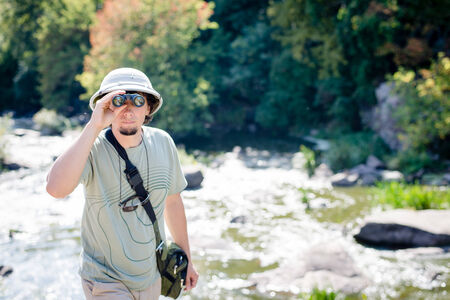 pith: Young curious man with spy glass wearing pith helmet at fast mountain river