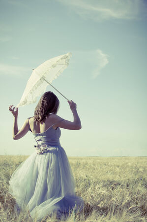 elegant romantic woman in long white dress having fun holding parasol standing back to camera on blue sky copy space background photo