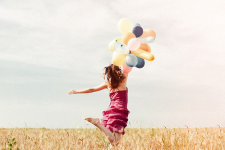 retro style photo: romantic blond young lady having fun holding air balloons flying in the field on summer blue sky outdoors copy space background