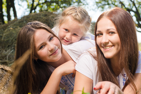 20 years old: Three happy sisters of 3, 13 and 20 years old lying at haystack looking at camera and smiling joyfully on summer park background Stock Photo