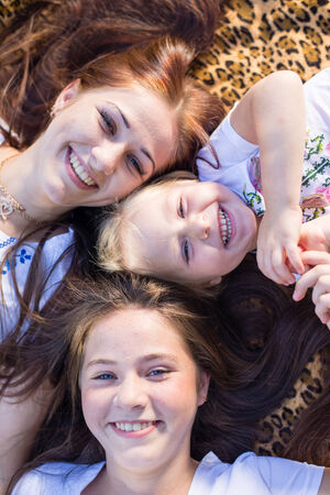 20 years old: Three happy sisters of 3, 13 and 20 years old lying on blanket looking up at camera and smiling joyfully