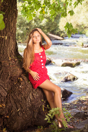 Young woman standing at willow tree by river and having fun on summer or early autumn outdoor copy space background photo