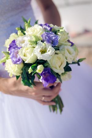 Wedding roses bouquet in bride hands closeup photo