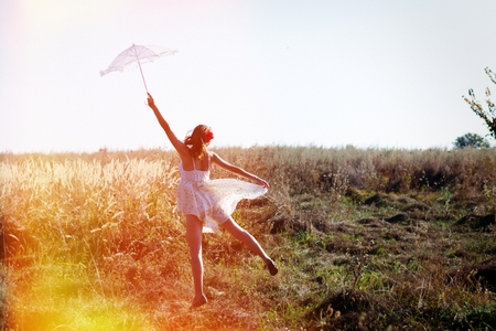 alone in the field: elegant romantic beautiful young lady in long white dress having fun holding up parasol standing back to camera on blue sky copy space background photo