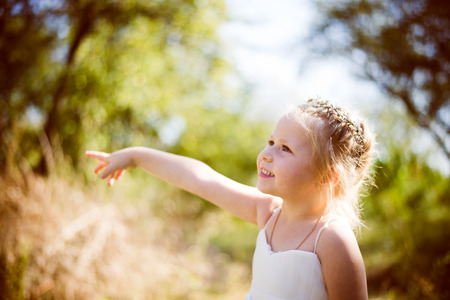 Cute little girl in white lace dress and princess diadem pointing on green summer outdoor copyspace background photo