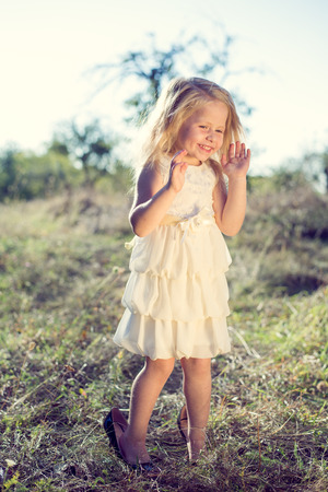 Portrait of happy little girl trying on sisters or moms high heel shoes and smiling on summer green path copy space background photo