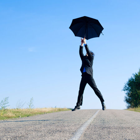 Image of businessman in formal suit flying on black umbrella or jumping over road against blue sky copy space background photo