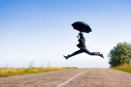 Image of businessman in formal suit flying in legs split on black umbrella or jumping over road against blue sky copy space background photo