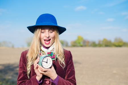 portrait of elegant beautiful blond young woman having fun holding retro alarm clock on sunny autumn outdoors copy space background photo