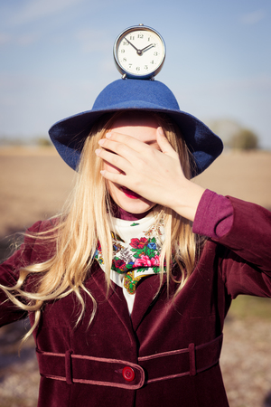 portrait of elegant beautiful blond young woman having fun holding retro alarm clock on the head eyes covered with hand on sunny autumn outdoors copy space background photo